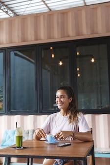 Retrato vertical de uma linda mulher sentar na mesa do café com smoothie e telefone celular.