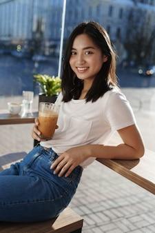 Retrato vertical de uma menina moderna feliz sentada em um café perto da janela e encostada na mesa, bebendo café com leite