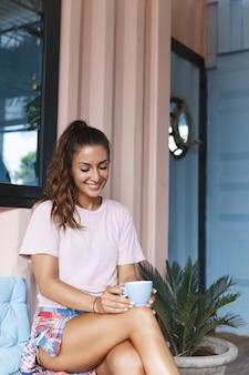 Retrato vertical de uma menina sorridente e relaxada, bebendo chá na varanda.