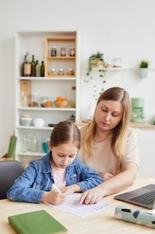 Retrato vertical de uma mulher adulta carinhosa, ajudando a menina a fazer o dever de casa ou a estudar em casa enquanto está sentada à secretária num interior acolhedor, copie o espaço
