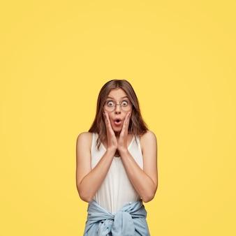 Retrato vertical de uma mulher europeia chocada reage a notícias inesperadas, olha fixamente com os olhos arregalados, suspiros de medo