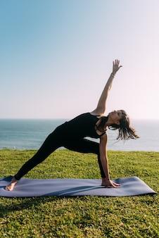 Retrato vertical de uma mulher magra praticando ioga fora de casa. copie o espaço