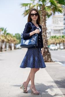 Retrato vertical de uma mulher segurando uma bolsa e usando óculos escuros