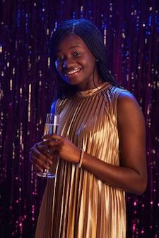 Retrato vertical de uma sorridente garota afro-americana segurando uma taça de champanhe e olhando para a câmera em pé contra um fundo cintilante na festa