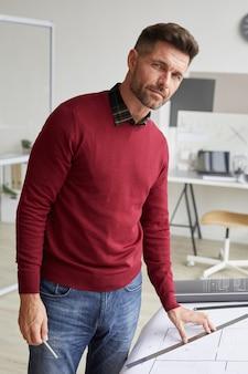 Retrato vertical do arquiteto barbudo maduro em pé na mesa de desenho no local de trabalho
