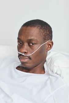 Retrato vertical em close de um homem afro-americano deitado em uma cama de hospital com tubos de oxigênio e olhando para a câmera