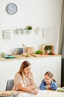 Retrato vertical em tons quentes de mãe carinhosa, ajudando a filha a fazer a lição de casa e a estudar em casa num interior acolhedor, copie o espaço