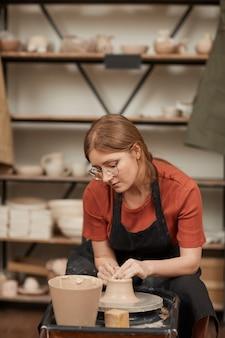 Retrato vertical em tons quentes de uma jovem moldando argila em uma roda de oleiro na oficina, enquanto desfruta de artes e ofícios, copie o espaço