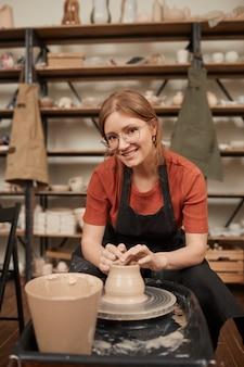 Retrato vertical em tons quentes de uma jovem oleira sorrindo para a câmera enquanto trabalhava na roda de oleiro na oficina e apreciava artes e ofícios, copie o espaço
