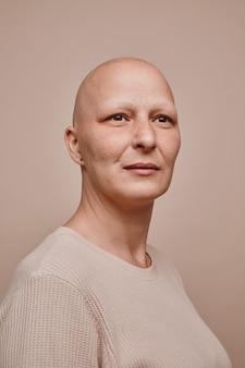 Retrato vertical em tons quentes de uma mulher careca confiante olhando para o lado esperançosamente enquanto posa contra um fundo bege mínimo em estúdio, alopecia e consciência do câncer