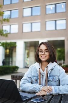 Retrato vertical inteligente bonita aluna em uma jaqueta jeans de óculos, sentar ao ar livre no banco, trabalhar no parque, trabalho freelance de meio período enquanto estudava na universidade, laptop e mesa de telefone móvel.
