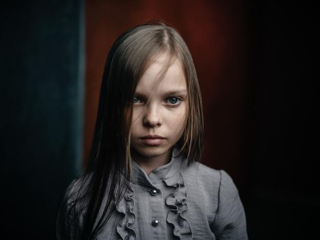 Retrato vintage de uma garota em um vestido em um fundo escuro.