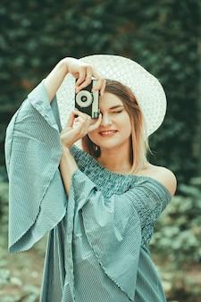 Retrato vintage jovem mulher espetacular no vestido e chapéu tira fotos com a câmera retro no fundo desfocado ao ar livre