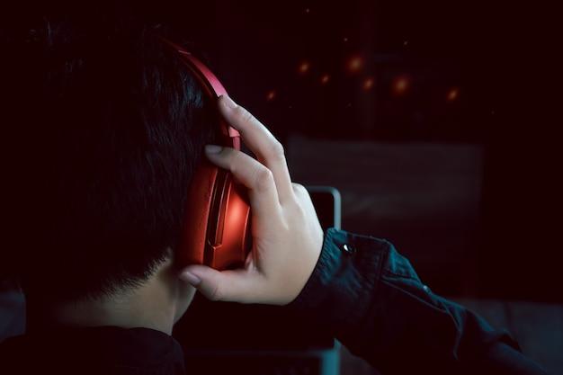 Retrato visto de trás e de trás de um orangotango humano usando fones de ouvido para ouvir música