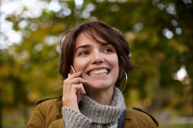 Retratof de uma linda jovem morena feliz com corte de cabelo curto, mantendo o celular na mão levantada enquanto tem uma conversa agradável, caminhando pelo jardim da cidade e sorrindo amplamente
