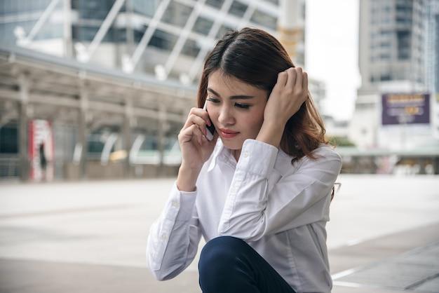 Retratos da bela mulher asiática, a confiança é de pé e segurando o celular