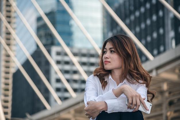 Retratos da bela mulher asiática estão segurando o sentimento de sensação de telefone inteligente pela depressão urbana.