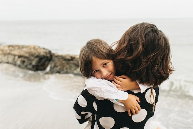 Retratos de mãe e filha na praia do mar