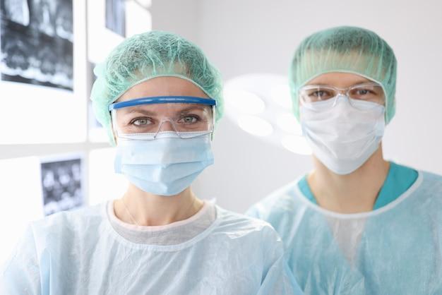 Retratos de médicos cirurgiões com roupas de proteção na clínica
