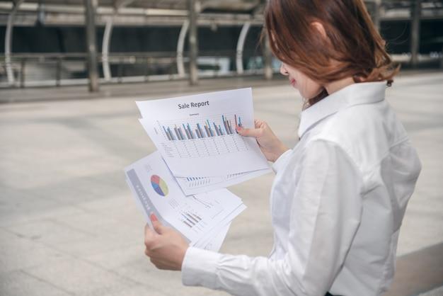 Retratos de mulher asiática bonita na expressão de pensamento trabalhando com documento de gráfico financeiro