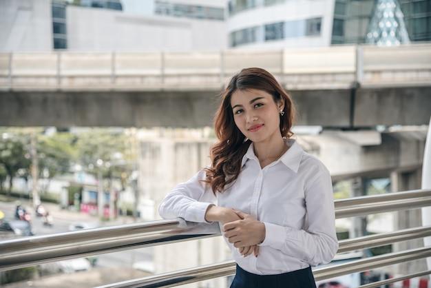 Retratos de mulher asiática bonita parecem alegres e a confiança está em pé ao ar livre