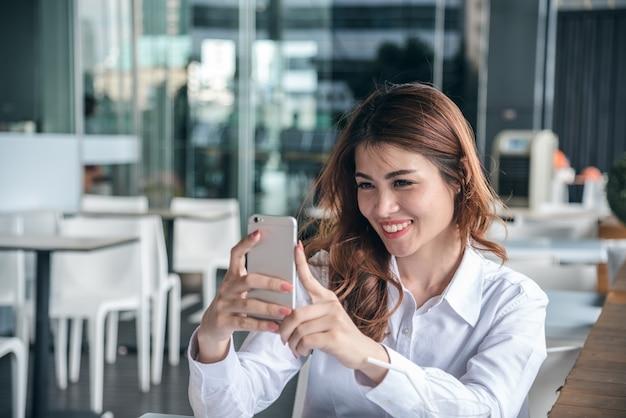 Retratos de pretty beautiful asian woman tomando uma foto por selfie em urbano.
