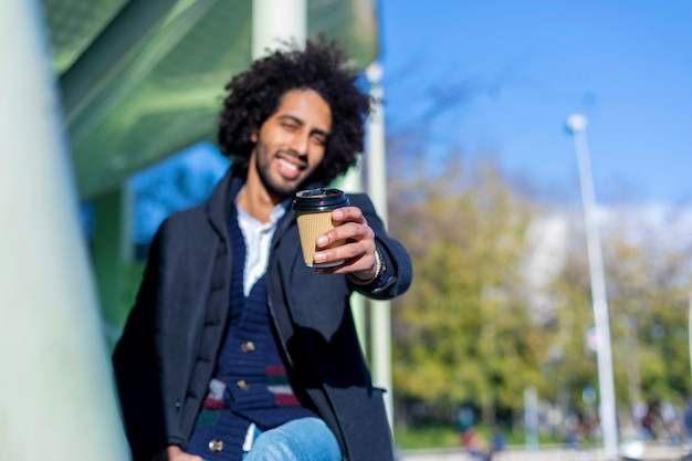Retratos de um homem afro sorridente bonito e elegante, sentado ao ar livre