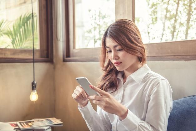 Retratos de uma bela mulher asiática, a confiança é segurando o celular.
