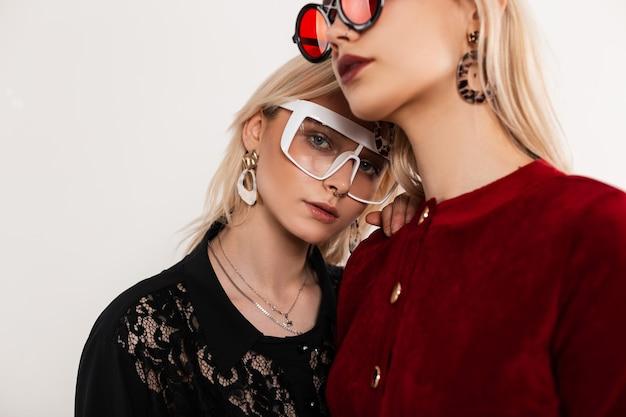 Retratos jovens lésbicas sensuais com roupas da moda preto-avermelhadas e óculos elegantes, lado a lado