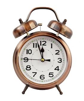 Retro o despertador da cor de bronze em doze horas isolado em um fundo branco. meia noite, meio dia. minutos sobre o ano novo.