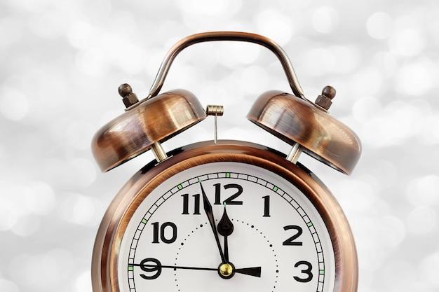 Retro o despertador de cor bronze às 12:00 no bokeh branco abstrato