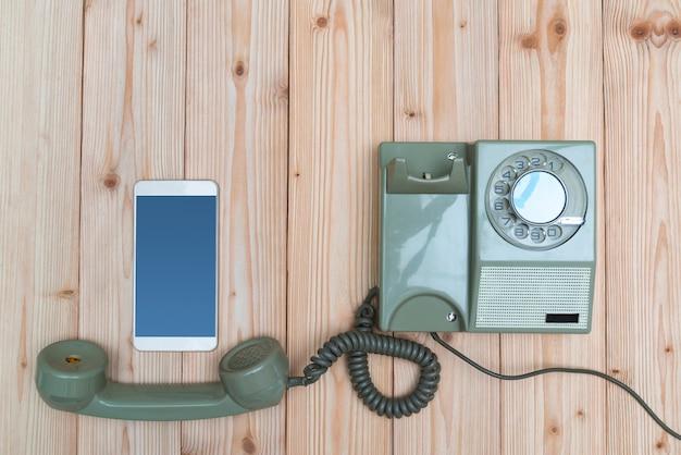 Retro telefone rotativo e novo celular ou telefone inteligente na madeira