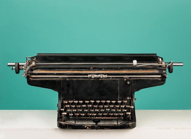 Retro velha máquina de escrever com papel na mesa de madeira