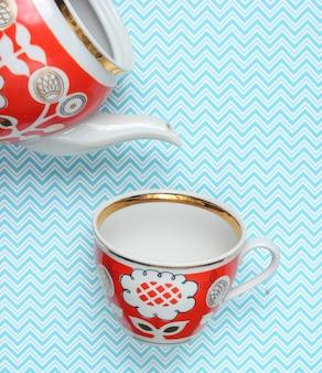 Retro xícara e bule com padrões vermelhos na toalha de mesa. vista do topo