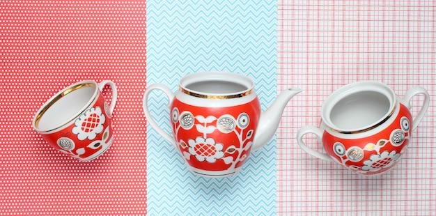 Retrô xícaras e bule com padrões vermelhos na toalha de mesa. vista do topo