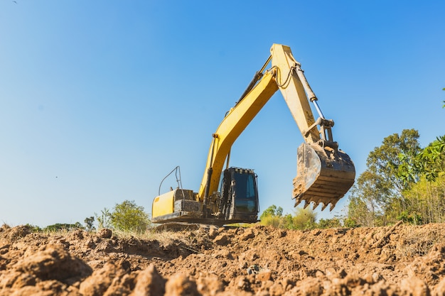 Retroescavadeira escavando o solo em um dia ensolarado