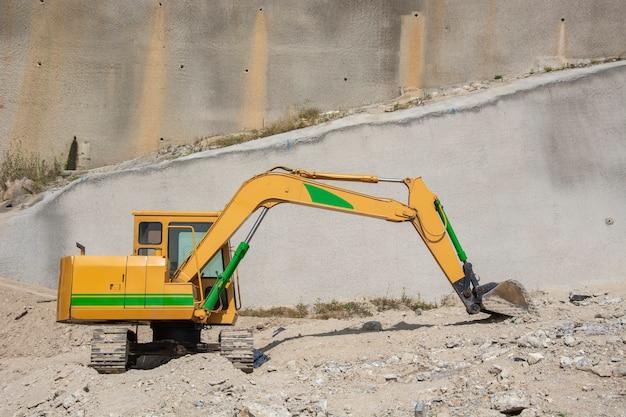 Retroexcavadora o maquinaria pesada para a construção em uma escavação