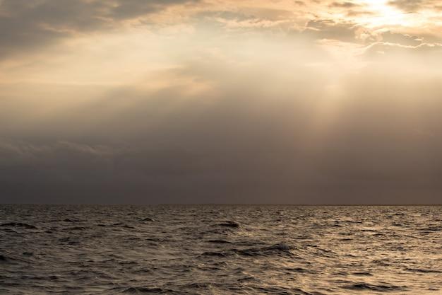 Retroiluminado do mar e do céu com a luz do sol brilha impacto.