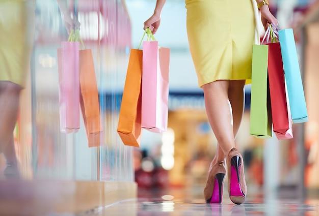 Retrovisor da mulher que anda pelo shopping