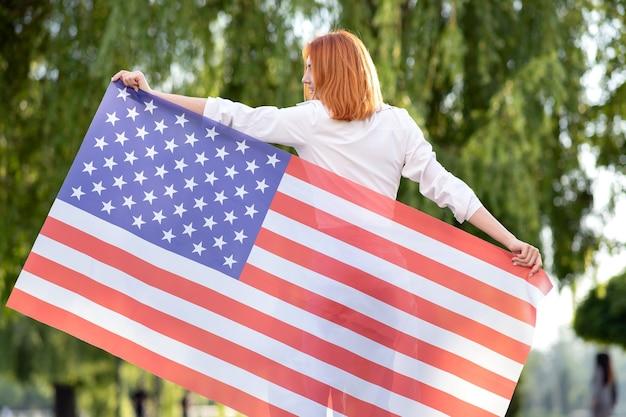 Retrovisor da mulher ruiva jovem feliz posando com a bandeira nacional dos eua em pé ao ar livre no parque de verão. menina positiva comemorando o dia da independência dos estados unidos.