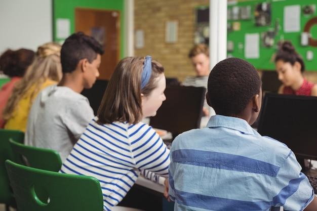 Retrovisor de alunos estudando em sala de aula de informática