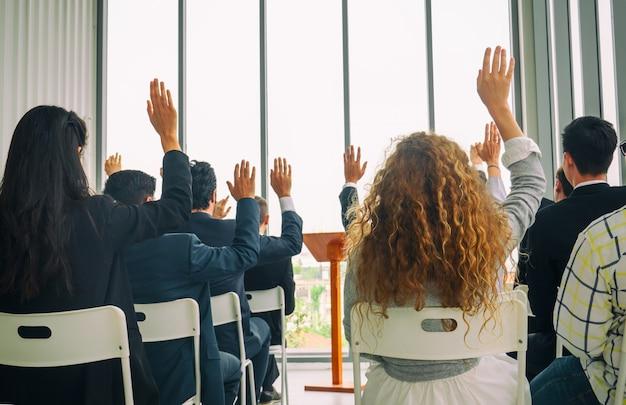 Retrovisor de empresários casuais levantando a mão para fazer a pergunta sobre evento educacional em um quadro