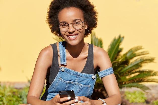 Retrovisor de mulher negra satisfeita com sorriso dentuço, usa óculos redondos, usa telefone inteligente para comunicação online, conectado à internet sem fio, descansa em local tropical. conceito de tecnologia