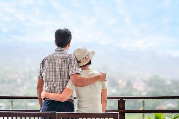Retrovisor de um feliz asiático de meia idade, um casal no banco