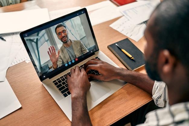 Retrovisor de um funcionário afro-americano de videoconferência com colega em briefing online, trabalhador do sexo masculino segurando webconferência com colega em um laptop moderno em casa