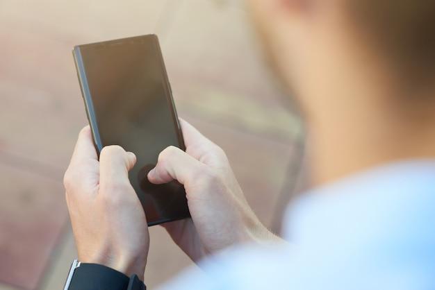 Retrovisor de um homem usando smartphone enquanto passa o tempo ao ar livre, focando no celular