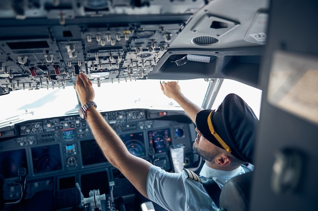 Retrovisor de um homem vestindo uniforme apertando botões na cabine durante o voo