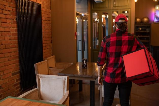 Retrovisor de um jovem mensageiro de flanela carregando uma grande sacola vermelha com pedidos de clientes saindo do café ou restaurante