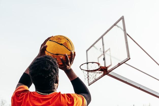 Retrovisor de um menino negro afro-americano pronto para atirar a bola na cesta.