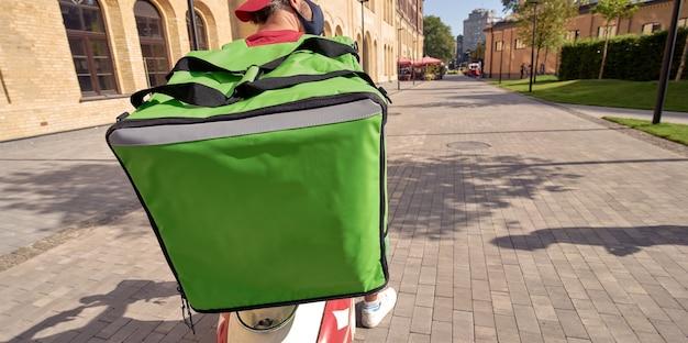 Retrovisor de um mensageiro com mochila térmica e máscara protetora preta andando de scooter